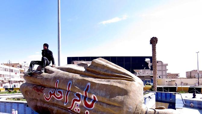 """FILE - In this Tuesday, March 5, 2013 file photo, citizen journalism image provided by Aleppo Media Center AMC which has been authenticated based on its contents and other AP reporting, shows Syrian man sitting on a fallen statue of former Syrian President Hafez Assad in a central square in Raqqa, Syria. The Arabic words on the fallen statue read: """"tomorrow will be better."""" A quiet power struggle in taking place in the eastern city between Islamic extremist rebels, who control the city after capturing it four months ago from the regime, and moderates trying to curtail their influence, making it a test case for the opposition.(AP Photo/Aleppo Media Center AMC, File)"""