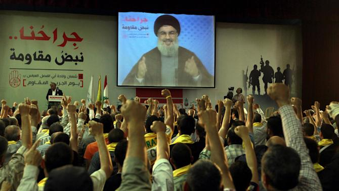 """Hezbollah supporters raise their hands in salute as Hezbollah leader Sheik Hassan Nasrallah speaks on a screen via a video link from a secret place, during a rally to mark the """"wounded resistants day,"""" in the southern suburb of Beirut, Lebanon, Friday, June 14, 2013. Nasrallah said his group will continue to fight in Syria """"wherever needed,"""" and said he has made a """"calculated"""" decision to defend Syria and is ready to bear all consequences.(AP Photo/Bilal Hussein)"""