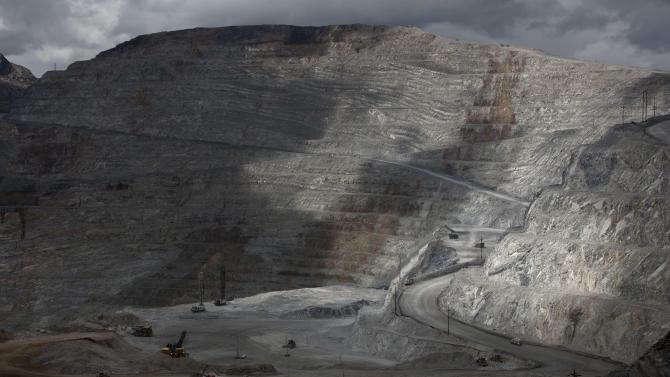 FILE - In this May 14, 2013 file photo, the open-pit Antamina mine in San Marcos, Peru, is partially illuminated on a cloudy day. A new law enacted July 11 by President Ollanta Humala, weakens environmental protections in the Andean nation as it prepares to host international climate-control talks. At the same time, it re-establishes tax breaks for big mining multinationals, which already enjoy such benefits as simultaneous, indefinite concessions for both exploration and exploitation as long as they make nominal payments. (AP Photo/Martin Mejia, File)
