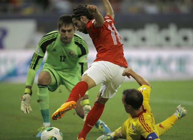 Turkey's Olcay Sahan, center, challenges Romania's Vlad Chiriches for the ball as goalkeeper Ciprian Tatarusanu, left, tries to block him during a World Cup Group D qualifying soccer match between Rom