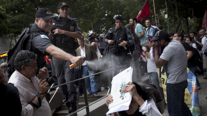 An activist shields herself as a police officer pepper sprays her during a protest outside a military club in downtown Rio de Janeiro, Brazil, Thursday March 29, 2012. A club of retired military officers held its annual celebration of Brazil's 1964 military coup as usual, but faced protestors as members arrived for the event. Unlike its Latin American neighbors, Brazil never had a formal investigation into its 20-year dictatorship. (AP Photo/Felipe Dana)