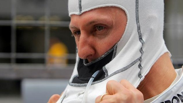 Mercedes Formula One driver Michael Schumacher of Germany puts on his balaclava before the Chinese F1 Grand Prix at Shanghai International circuit April 15, 2012