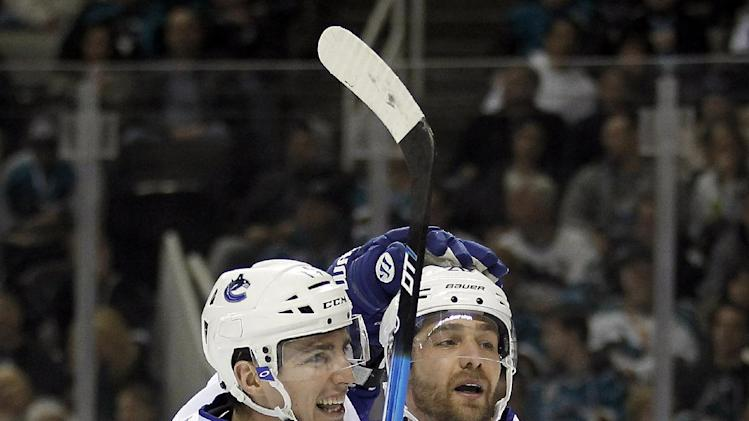 Vancouver Canucks center Alex Burrows (14) celebrates with left wing Chris Higgins (20) after scoring a goal against the San Jose Sharks during the second period of an NHL hockey game in San Jose, Calif., Sunday, Jan. 27, 2013. (AP Photo/Tony Avelar)