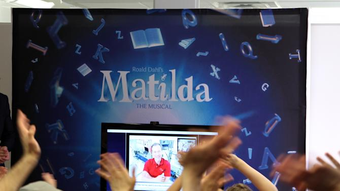 "This May 7, 2013 photo shows the cast of the Tony Award-nominated ""Matilda"" waving to Tim Marshburn, one of six astronauts aboard the International Space Station, via a satellite hook-up provided by NASA, at a gathering in New York. Cast members, including many children, packed a small room near Times Square on Tuesday to ask questions about life in space.  (AP Photo/Mark Kennedy)"