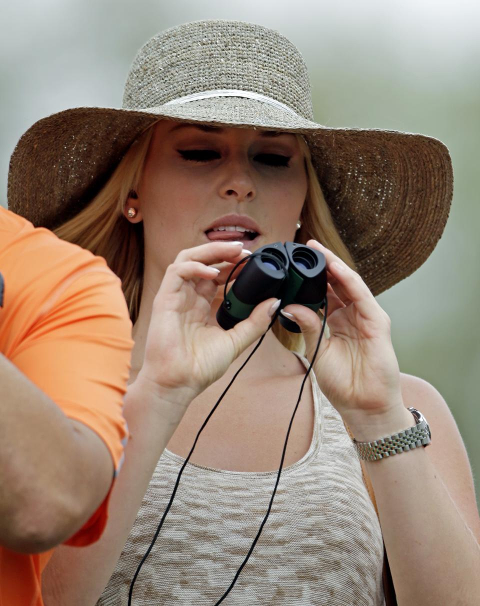 Skier Lindsey Vonn tries a pair binoculars to watch Tiger Woods during the first round of the Masters golf tournament Thursday, April 11, 2013, in Augusta, Ga. (AP Photo/Darron Cummings)