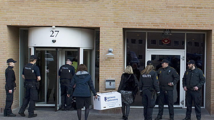 Danish Police secure the entrance as lawyer assistants arrive at the court in Copenhagen, Denmark, Friday April 13, 2012, carrying an evidence box prior to the start of a court case against four men accused of terrorism and illegal possession of weaponry.  The terror trial of four Swedes accused of plotting a revenge attack on Danish newspaper Jyllands-Posten that printed caricatures of the Prophet Muhammad, started Friday in Denmark, with a heavily armed police presence. (AP PHOTO/POLFOTO, Kenneth Meyer)  DENMARK OUT