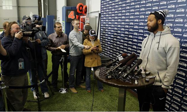 Seattle Seahawks defensive end Michael Bennett, right, talks to reporters, Monday, March 10, 2014, at the team's headquarters in Renton, Wash. The Seahawks announced Monday that Bennett, who was o