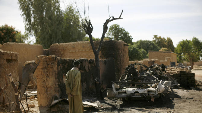 An elderly man looks at the charred remains of a truck used by radical Islamists on the outskirts of Diabaly, Mali, some 460kms (320 miles) North of the capital Bamako, after French and Malian troops took control of the town Monday, Jan. 21, 2013. (AP Photo/Jerome Delay)