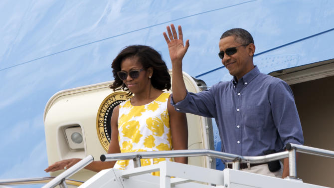 President Barack Obama and first lady Michelle Obama wave as they arrive in Cape Cod, Mass., to fly via helicopter to begin their family vacation in Martha's Vineyard on Saturday, Aug. 10, 2013. (AP Photo/Jacquelyn Martin)