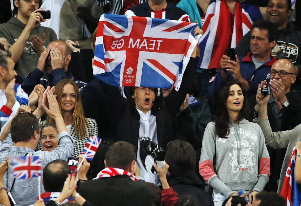 Performer Paul McCartney, center, celebrates Britain's gold medal wins alongside his daughter Stella, center left, and wife Nancy Shevell, center right, during the athletics in the Olympic Stadium at the 2012 Summer Olympics, London, Saturday, Aug. 4, 2012. (AP Photo/Matt Dunham)