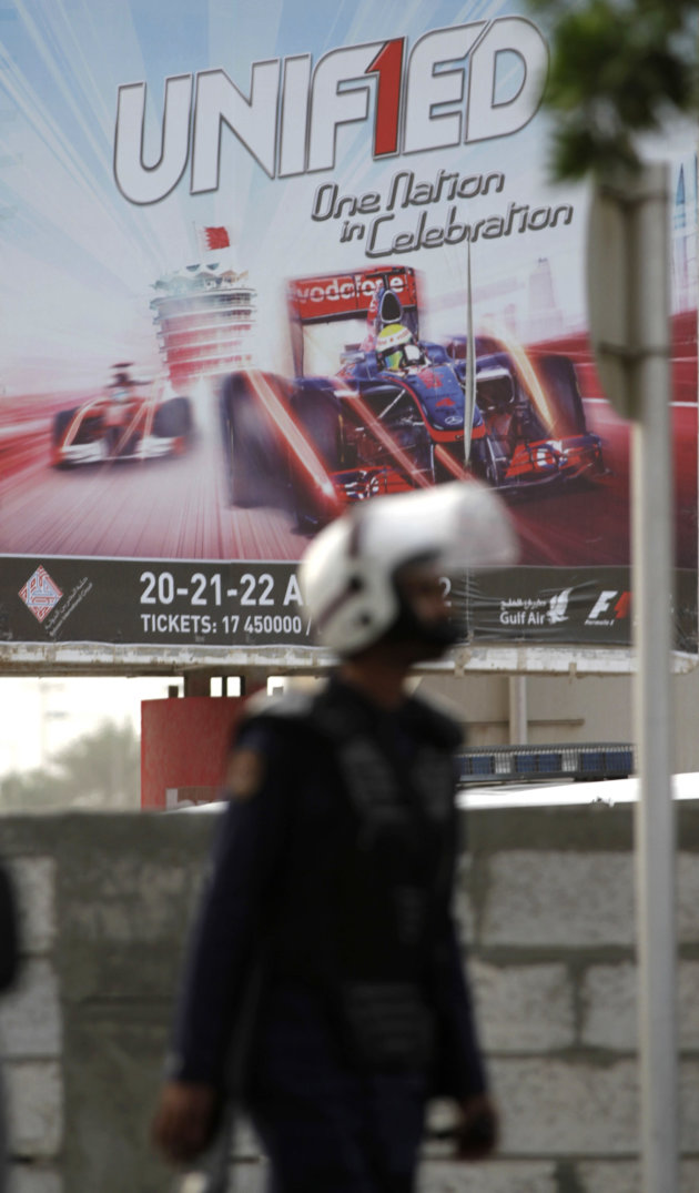 A riot police officer walks past an advertising board promoting Sunday's Formula One Grand Prix in Manama, Bahrain, Thursday, April 19, 2012. Nervous shop owners closed their doors and security forces