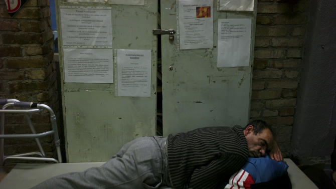In this photo taken early morning Friday, Jan. 11, 2013, a homeless man sleeps on a mattress in a shelter called 'The Heated Street' in Budapest, Hungary. Hungary considers constitutional change to allow authorities to force homeless off the streets. (AP Photo/Bela Szandelszky)