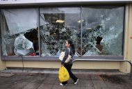 A woman walks past a damaged supermarket in Ealing, west London, after a night of rioting, Tuesday, Aug. 9, 2011. In London, groups of young people rampaged for a third straight night, setting buildings, vehicles and garbage dumps alight, looting stores and pelting police officers with bottles and fireworks into early Tuesday. The spreading disorder was an unwelcome warning of the possibility of violence during London's 2012 Summer Olympics, less than a year away. (AP Photo/Lefteris Pitarakis)