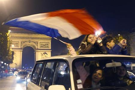 France soccer fans celebrate with their country's flag near the Arc de Triomphe on the Champs Elysees in Paris after France defeated Ukraine in their 2014 World Cup qualifying second leg playoff socce