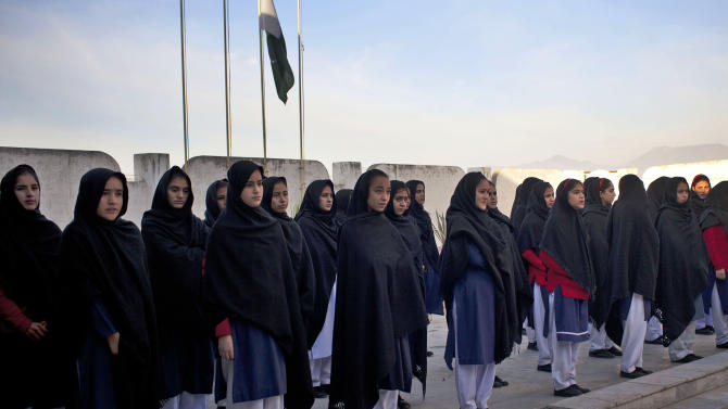 In this Thursday, Nov. 15, 2012 photo, Pakistani school children line up under the Pakistani flag before attending class at the Khushal School for Girls in Mingora, Swat Valley, Pakistan. Malala Yousufzai attended Khushal School when a Taliban gunman shot her and her two friends, Shazia Ramazan and Kainat Riaz. Malala was shot for her outspoken insistence on girls education. Shazia and Kainat are to return to school this week for the first time since the shooting more than one month ago. ( AP Photo/Anja Niedringhaus)