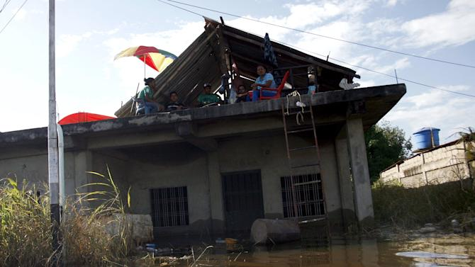 People sit on the roof of a house on a flooded street in Guasdualito, in the state of Apure, Venezuela