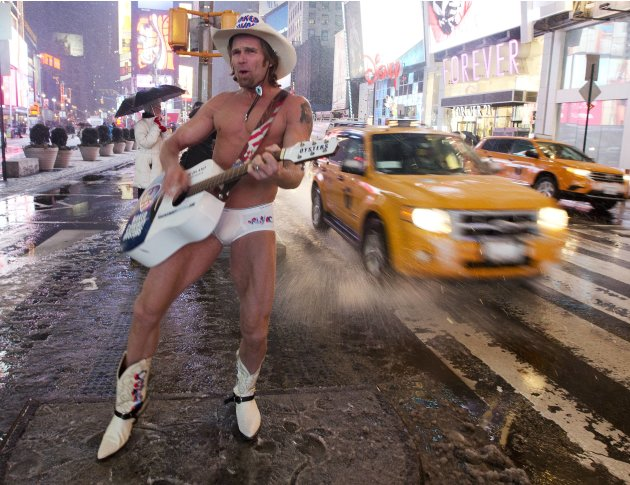 "Robert Burck, aka the ""Naked Cowboy,"" performs in Times Square as it snows Friday, Feb. 8, 2013, in New York. Snow began falling across the Northeast on Friday, ushering in what was predicted to be a"