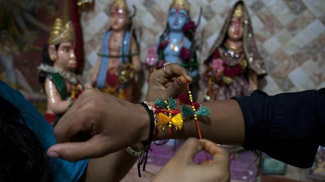 """A Pakistani Hindu girl ties Rakhi or ceremonial thread on the wrist of her brother during a Raksha Bandhan festival at a temple in Karachi, Pakistan, Saturday, Aug. 29, 2015. The festival celebrates the love and duty between """"brothers and sisters"""" and symbolic gifts are exchanged between siblings but is not limited to biological relatives. (AP Photo/Shakil Adil)"""