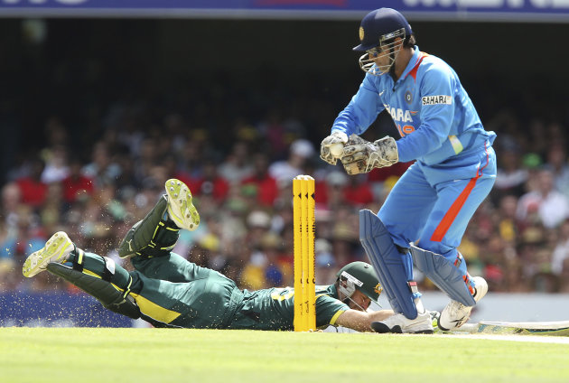 Australia's Matthew Wade (on the ground) slides home safely as India's wicket keeper MS Dhoni, right, attempts to run him out during the One Day International cricket match between Australia and India
