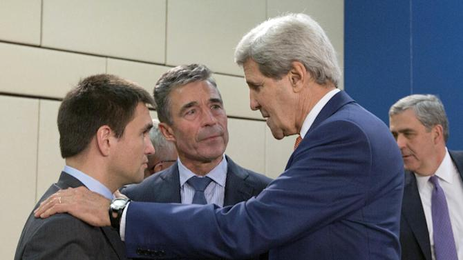 Ukrainian Foreign Minister Pavlo Klimkin, left, speaks with NATO Secretary General Anders Fogh Rasmussen, center, and U.S. Secretary of State John Kerry, second right, during a meeting of the NATO-Ukraine Commission at NATO headquarters in Brussels on Wednesday, June 25, 2014. Wednesday's meeting will discuss how NATO can help build Ukraine's military capacities, including by creating targeted trust funds. (AP Photo/Virginia Mayo)