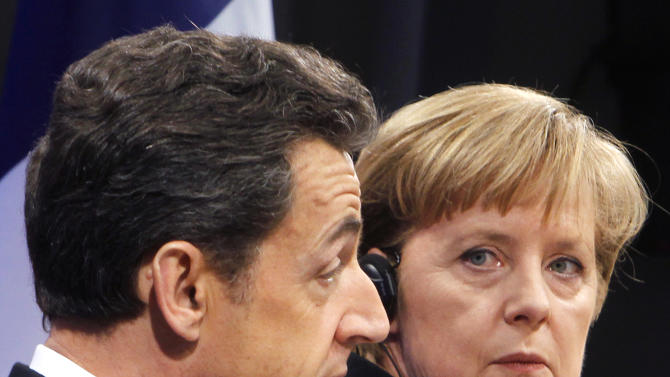 FILE - In this Dec. 10, 2010 file photo, French President Nicolas Sarkozy and German Chancellor Angela Merkel talk at a press conference during the German-French consultations in Freiburg, Germany. Chancellor Merkel travels to Paris Tuesday Aug. 16, 2011, armed with plans for a new EU body to enforce strict budget limits and fiscal policy and calls for all eurozone nations to enshrine a balanced budget in their constitution. (AP Photo/Michael Probst,File)