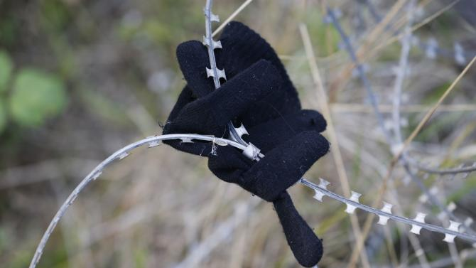 A glove left by a migrant is seen on razor-wire near train tracks which lead to the Channel Tunnel in Frethun, near Calais