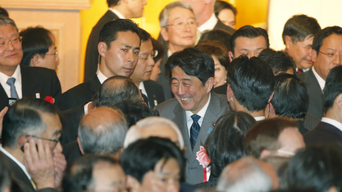 In this photo taken Monday, Jan. 7, 2013. Japanese Prime Minister Shinzo Abe, center, smiles as he talks with business leaders as he attends a joint New Year's party by Japan's business organizations in Tokyo. Japan's ruling Liberal Democratic Party was in the final stages of drafting fresh stimulus spending Thursday, Jan. 10, reportedly totaling more than 20 trillion yen ($227 billion), rushing to fulfill campaign pledges to break the world's third-biggest economy out of its deflationary slump. Economy minister Akira Amari and Abe discussed details of the proposed stimulus package ahead of an announcement expected on Friday, officials said. (AP Photo/Shizuo Kambayashi)