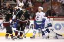 Arizona Coyotes' Tobias Rieder (8), of Germany, celebrates his goal against Vancouver Canucks' Eddie Lack (31) with teammate Mark Arcobello (36) as Canucks' Ryan Stanton (18) dejectedly skates near the celebration during the first period of an NHL hockey game Thursday, March 5, 2015, in Glendale, Ariz. (AP Photo/Ross D. Franklin)