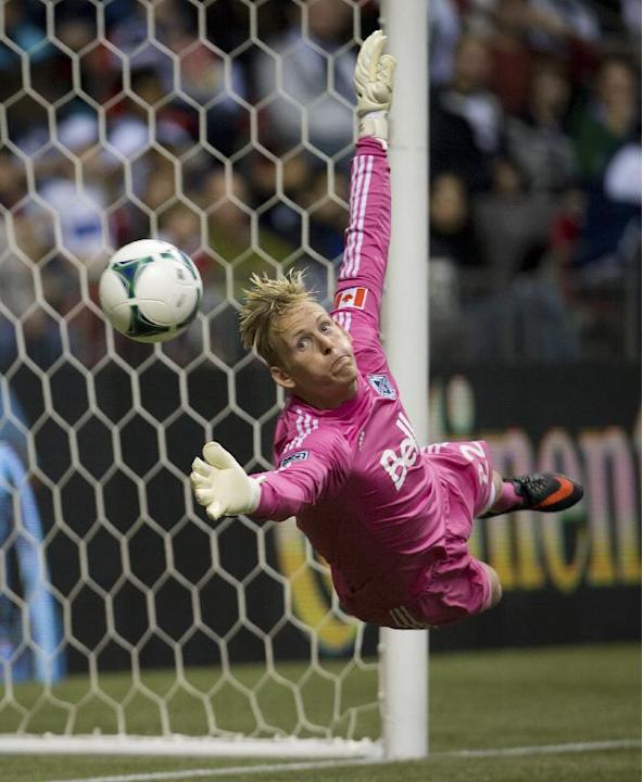 Vancouver Whitecaps goalkeeper David Ousted, of Denmark, dives to stop a Real Salt Lake shot on goal during the second half of an MLS soccer game Saturday, Sept. 28, 2013, in Vancouver, British Columb