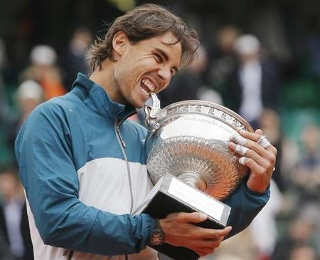 Nadal of Spain bites the trophy after defeating compatriot Ferrer in their men's singles final match to win the French Open tennis tournament in Paris