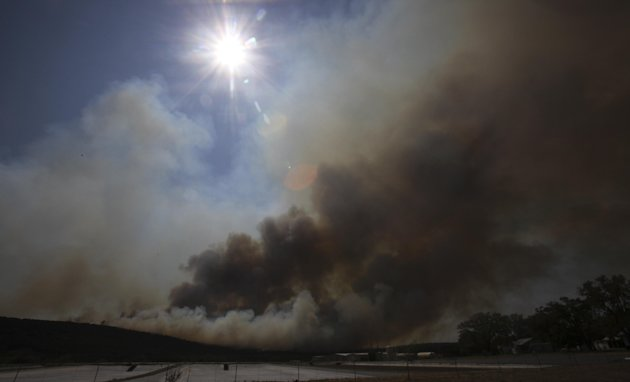 Smoke rises from a wildfire at Possum Kingdom Lake, Texas, Wednesday, Aug. 31, 2011.   Texas and Oklahoma are in the grips of a record-setting drought, and a summer of soaring temperatures and little