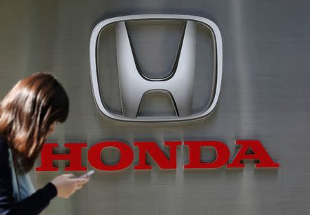 File photo of a woman using her mobile phone as she walks past a Honda Motor Co. logo outside the company's dealership in Tokyo