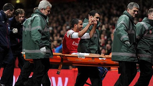 Theo Walcott gestures to the Tottenham fans as he's carried off