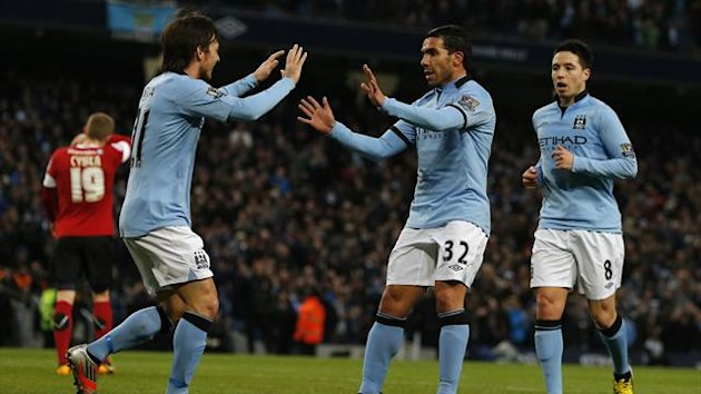 Manchester City's Carlos Tevez (2nd R) celebrates after scoring his team's third goal during their FA Cup quarter-final against Barnsley (Reuters)
