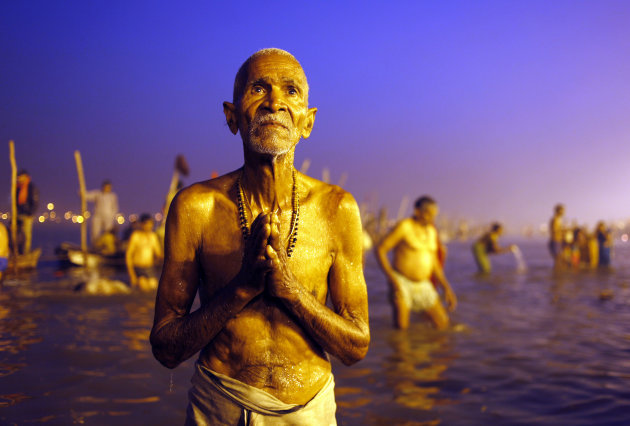 A Hindu devotee prays after a holy dip at 'Sangam', the confluence of Hindu holy rivers Ganges, Yamuna and the mythical Saraswati, during the Maha Kumbh festival at Allahabad, India, Sunday, Feb. 10, 