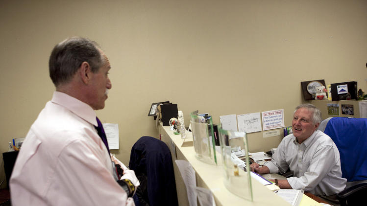 In this Feb. 15, 2012 photo, Steve Wyard, right, a 61-year-old regional sales director at All Valley Washer Service, chats with his colleague Larry Erlichman in their office in the Van Nuys section of Los Angeles. Wyard and his wife have two sons, 19 and 21, to put through college, and they see that pushing back retirement for several years. Until then Wyard plans to keep working. (AP Photo/Jae C. Hong)