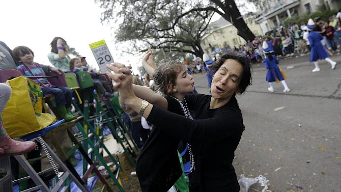 Mirella Reilly, of New Orleans, dances with her daughter Luciana Reilly, 6, as a marching band passes during the Krewe of Mid-City Mardi Gras parade in New Orleans, Sunday, Feb. 10, 2013. (AP Photo/Gerald Herbert)