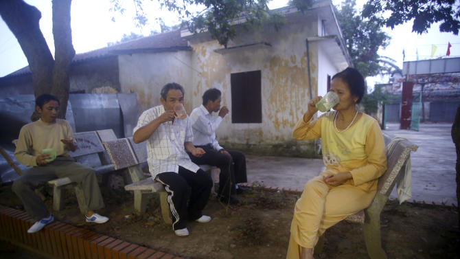 In this photo taken March 18, 2013, patients at the Scientology Health Center of the Vietnam Association of Agent Orange Victims take a dose of 35 vitamins in the early morning in Thai Binh, Vietnam. The center runs a 25-day health program which, as well as massive consumption of vitamins, includes four-hour sauna sessions and a morning run. While there is no medical evidence that the treatment at the center is effective, Vietnamese authorities are supporting it as a way of relieving some of the suffering of the between 2 and 4 million people suffering from illnesses linked to exposure to Agent Orange during the war. (AP Photo/Na Son Nguyen)