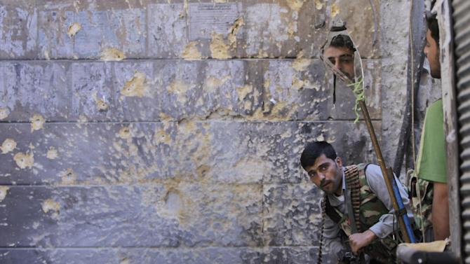 FOR USE AS DESIRED, YEAR END PHOTOS - FILE - In this Sept. 24, 2012 file photo, a Free Syrian Army soldier, right, looks through a mirror which helps him see Syrian troops from the other side, as he takes his position with his comrade during fighting, at the old city of Aleppo city, Syria.  (AP Photo/Hussein Malla, File)