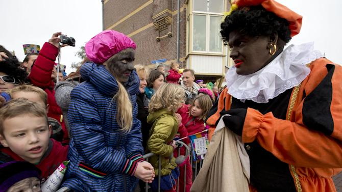 """Children, some with faces painted black, wait for """"Zwarte Piet"""" or """"Black Pete"""", right, to hand them candy after they arrived with Sinterklaas, or Saint Nicholas, in Hoorn, north-western Netherlands, Saturday Nov. 16, 2013. The tradition of Sinterklaas, the Dutch version of Santa Claus, is the subject of debate, where opponents say Black Petes are an offensive caricature of black people while supporters say Pete is a figure of fun whose appearance is harmless, his face soot-stained from going down chimneys to deliver present for the children. (AP Photo/Peter Dejong)"""