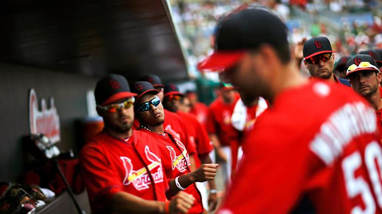 Teammates wait to fist-bump St. Louis Cardinals starting pitcher Adam Wainwright, right, as he walks into the dugout upon being relieved in the fifth inning of an exhibition spring training baseball game against the New York Mets, Sunday, March 16, 2014, in Jupiter, Fla