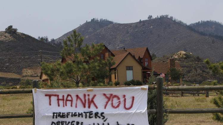 A sign thanking firefighters is attached to a fence of a home that was surrounded by fire on the High Park wildfire near Bellvue, Colo., on Monday, June 18, 2012. The wildfire has burned over 180 homes.  (AP Photo/Ed Andrieski)