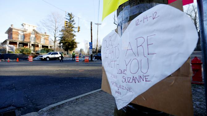 A sign on a post shows support for the victims of a gunman who opened fire inside Sandy Hook Elementary School a day earlier as police officers stand at a road block, Saturday, Dec. 15, 2012, in Sandy Hook village of Newtown, Conn. The massacre of 26 children and adults at Sandy Hook Elementary school elicited horror and soul-searching around the world even as it raised more basic questions about why the gunman, 20-year-old Adam Lanza, would have been driven to such a crime and how he chose his victims.  (AP Photo/Julio Cortez)