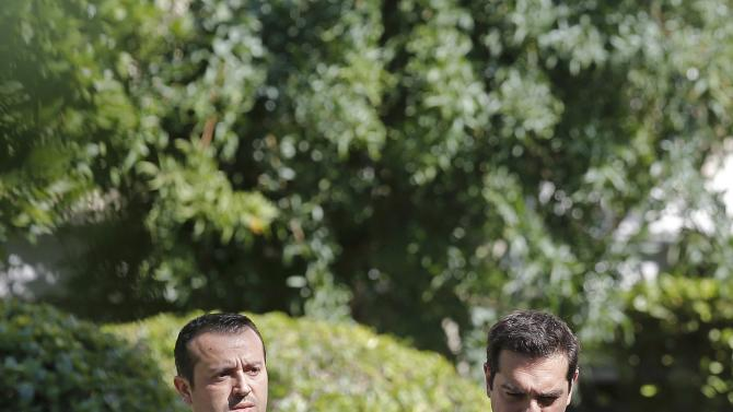Greek Prime Minister Tsipras and Minister of State Papas leave the Presidential Palace for Maximos Mansion after a meeting with party leaders in central Athens