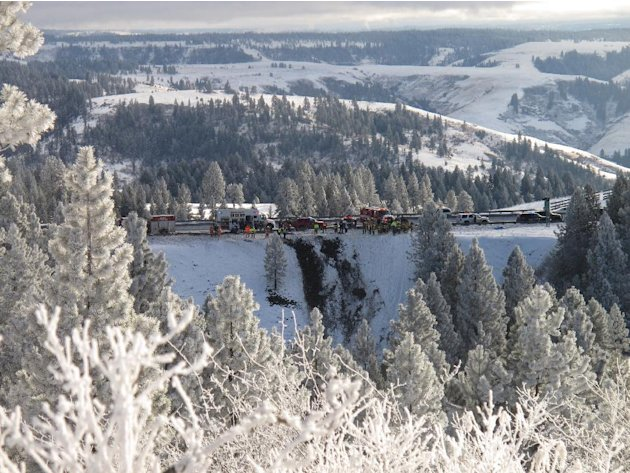 Emergency personnel respond to the scene of a multiple fatality accident where a tour bus careened through a guardrail along an icy Oregon highway and several hundred feet down a steep embankment, aut