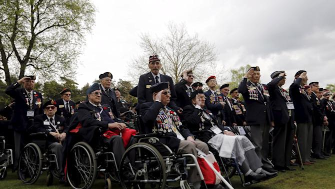 Canadian WWII veterans salute during the playing of the last post at a ceremony on the eve of the 70th anniversary of the liberation of the Netherlands at the Canadian War Cemetery in Holten