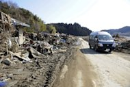 A police van moves carefully along a road past damaged homes and amongst piles of debris left by the tsunami in 2011. Five people were killed when a van carrying elderly evacuees from Japan's Fukushima nuclear accident collided head-on with a truck Saturday, local police and a report said