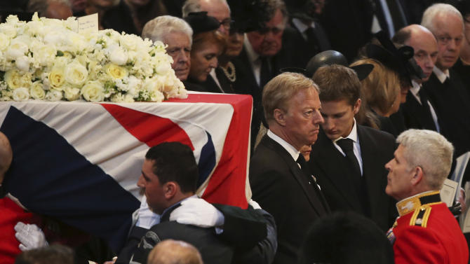 Mark Thatcher stares ahead, as others watch the coffin of his mother, former British Prime Minister Baroness Thatcher being carried from St Paul's Cathedral on  in London, England, Wednesday April 17, 2013. Dignitaries from around the world today join Queen Elizabeth II and Prince Philip, Duke of Edinburgh as the United Kingdom paid tribute to Thatcher during a Ceremonial funeral with military honours. Lady Thatcher, who died last week, was the first British female Prime Minister and served from 1979 to 1990.  (AP Photo/Christopher Furlong, Pool)