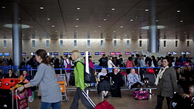 """Passengers wait in a departure hall at the Ben Gurion airport near Tel Aviv, Israel, Sunday, April 21, 2013. Israel's three airlines went on strike Sunday over a proposed """"Open Skies"""" deal with the European Union that union workers say jeopardizes their jobs and could even cause the local airline industry to collapse. (AP Photo/Ariel Schalit)"""