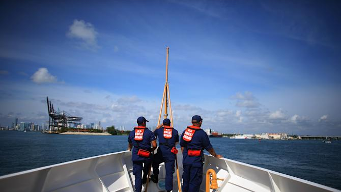 Coast Guard personnel are seen on their boat as they arrive back in Miami Beach